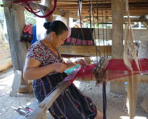 Weberin arbeitet im Schatten des Pfahlhauses. Früher hatten die Leute im Dorf auch eine Seidenraupenzucht, diese wurde mittlerweile aufgegeben, da die Seide günstiger gekauft werden kann.